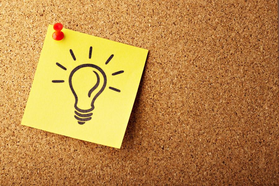 A Lightbulb drawn on a sticky note pinned to a corkboard